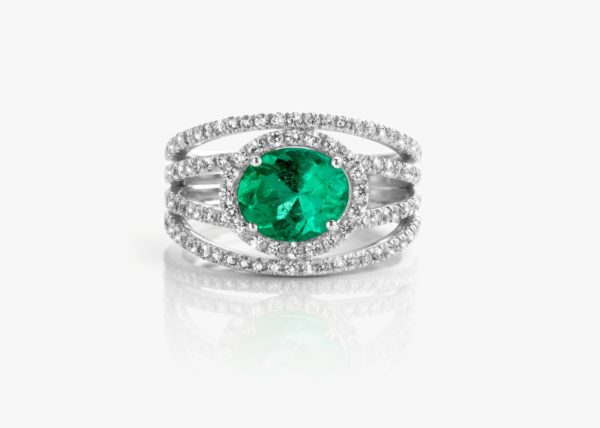 White gold ring, set with an oval-cut emerald and framed by diamonds