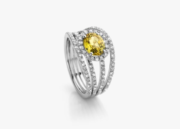 White gold ring, set with a yellow oval-cut sapphire and framed by diamonds