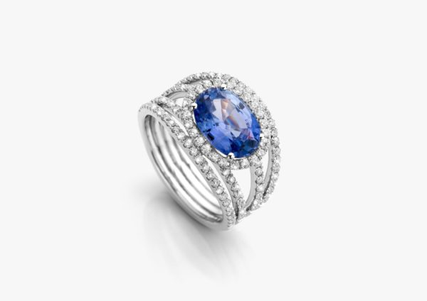 White gold ring, set with an oval-cut sapphire and framed by diamonds