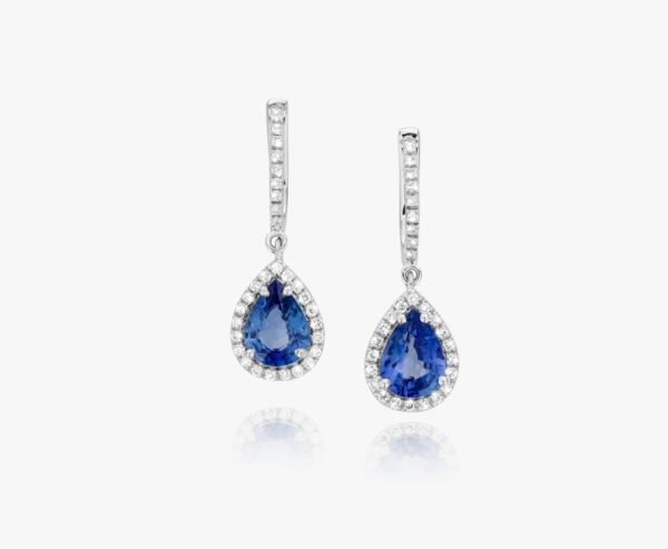 White gold earrings, set with an oval-cut sapphire and framed by diamonds