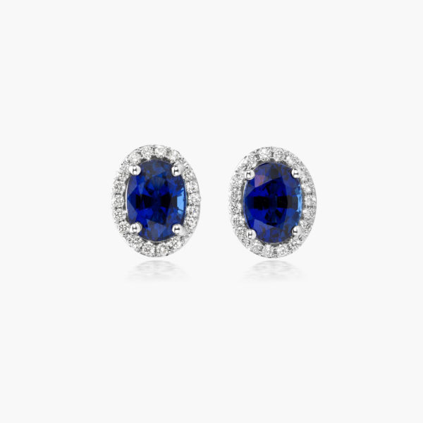 White gold earrings set with an oval shaped blue sapphire and brilliant cut diamonds