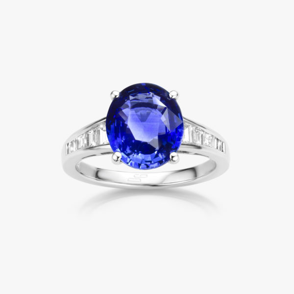 White gold ring set with oval shaped blue sapphire and emerald shaped diamonds